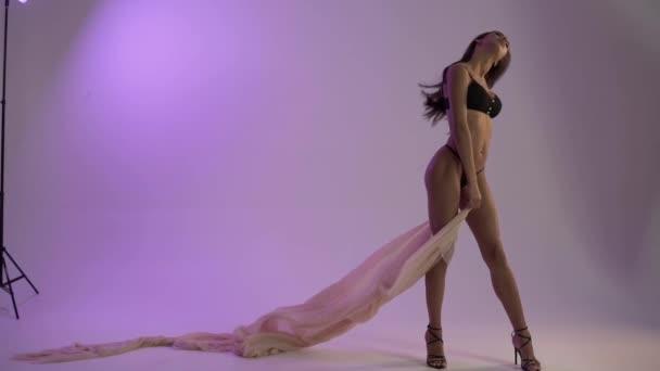 Belle linee del corpo, ragazza in bikini con stoffa in studio