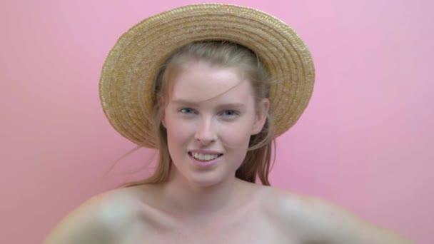 Gyönyörű tizenéves lány, vörös hajú, kék szeme a rózsaszín háttér