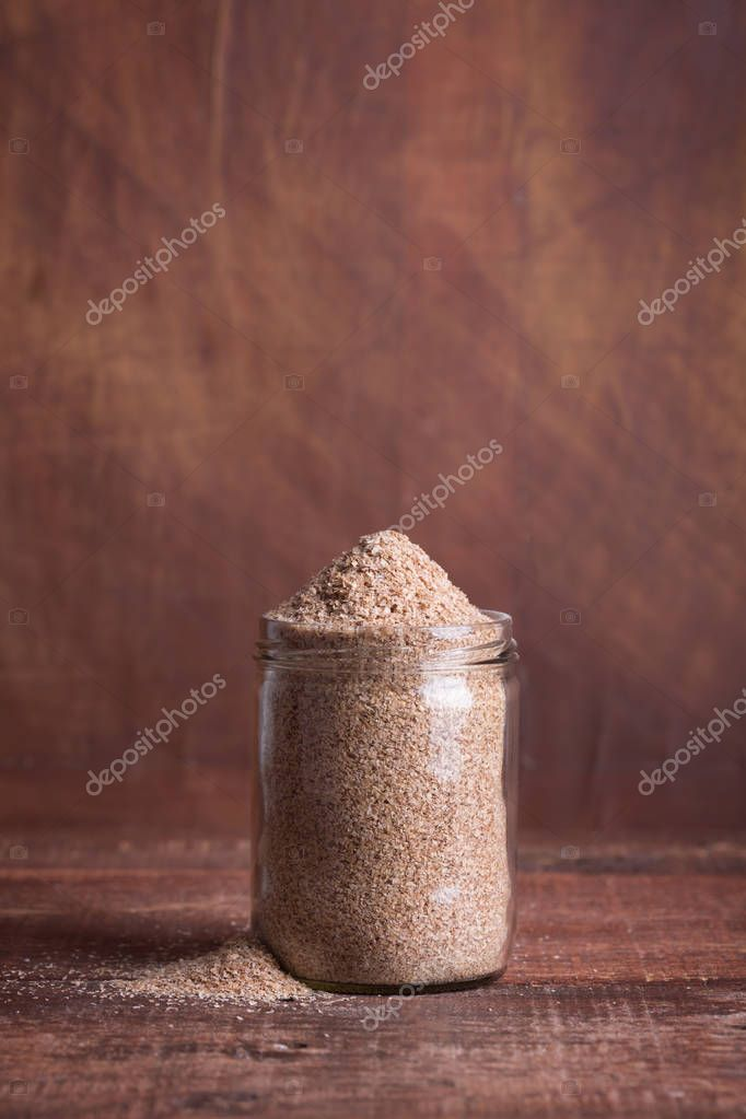 Dry bran in a glass jar on a wooden surface