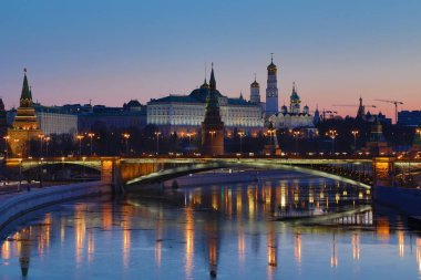 Illuminated Moscow Kremlin and Bolshoy Kamenny Bridge in the rays of rising sun. View from the Patriarshy pedestrian Bridge in Russia. Morning urban landscape in the blue hour