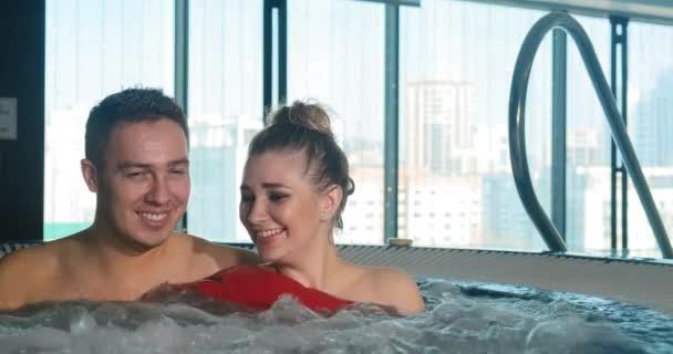 freudiges Paar lacht und umarmt sich im Whirlpool