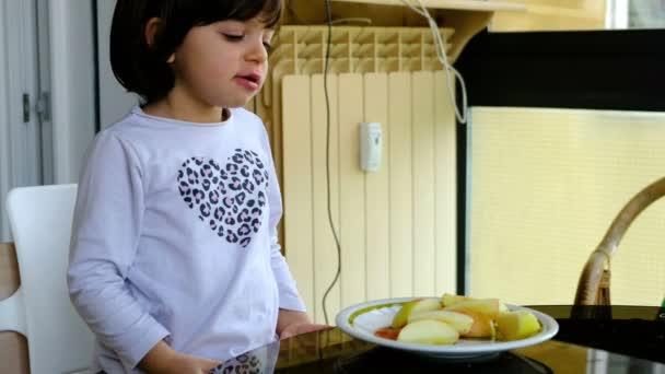 baby girl eat apple fruit slices - healthy snack child