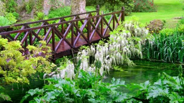 tündérmese híd élénk zöld folyó fa tele virágokkal díszkert
