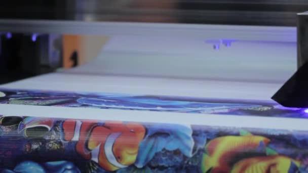 Videozáznamu z průmyslové tiskárny. Tisk barevný nápis na lepidlo na folie.
