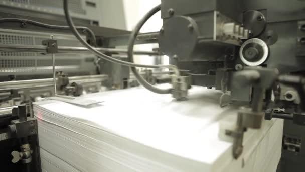 Videoklip z tisku továrny. Stroj pro podávání papíru v provozu. Podrobnosti o moderní vybavení.