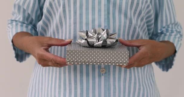 Ženské ruce dává dárek v krabičce s mašlí