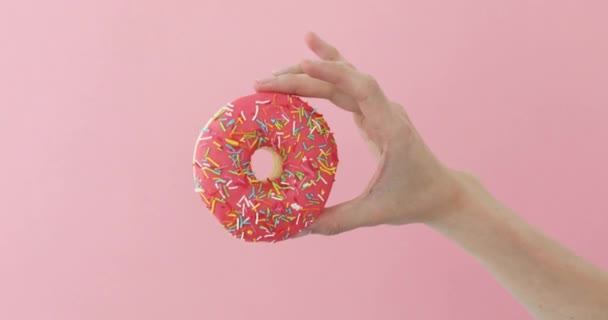 Womens hand holding donut on pink background