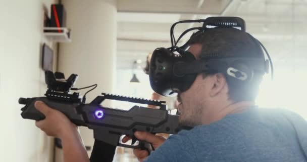 Guy playing VR sniper game with gun and glasses