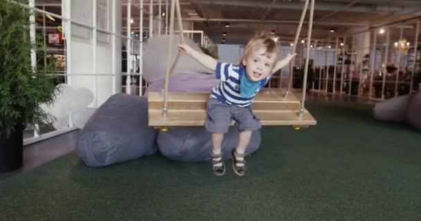 Malý roztomilý kluk baví na houpačky