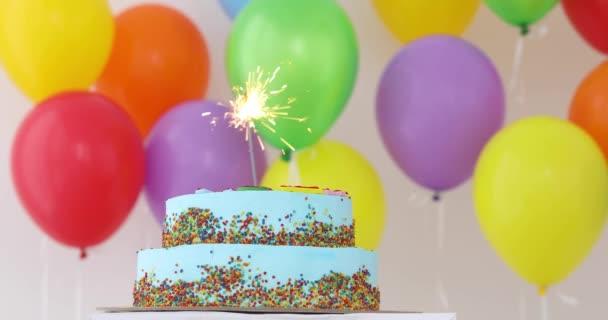 Kék születésnapi torta csillagszóró és színes léggömbök