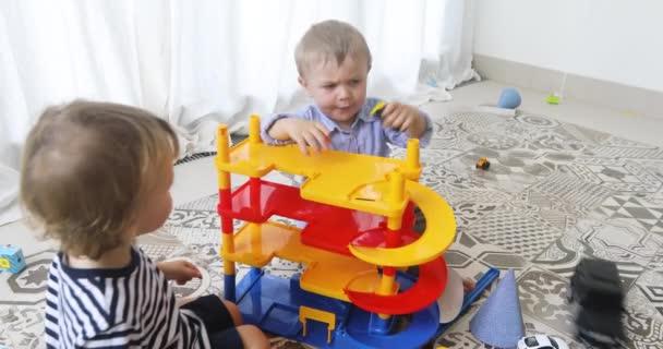 Šťastné děti hrají s autíčky na podlahu