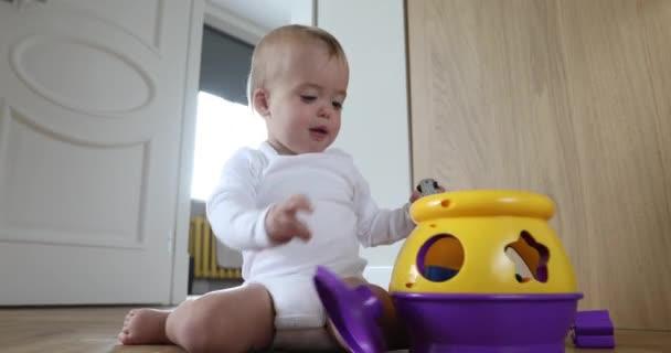 Roztomilé dítě hrát s barevnými hračkami, sedí na podlaze