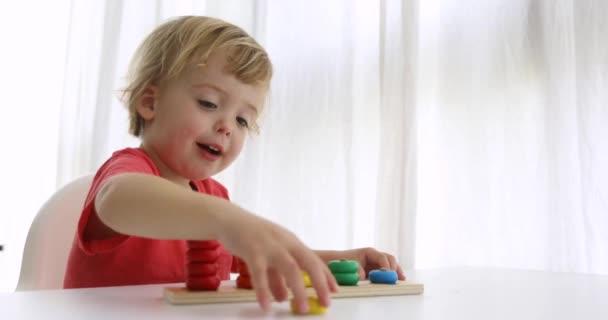 Kluk hraje s dřevěnými rozvíjející puzzle hračky