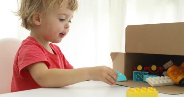 Malý chlapec uklizení své hračky v krabici