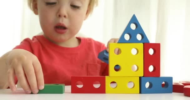 Dítě staví dům. Okouzlující dítě chlapec sedí u stolu a hrát si s barevnými konstruktor bloky na bílém pozadí