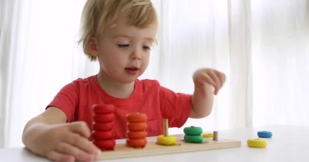 Kluk hraje s dřevěné hračky rozvíjející puzzle. Vzdělávací dětské hračky pro školky a školky
