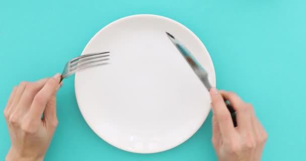 Ženské ruce s příbory a prázdný talíř