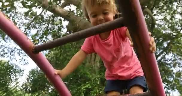 Zufriedener Junge klettert auf Spielplatz