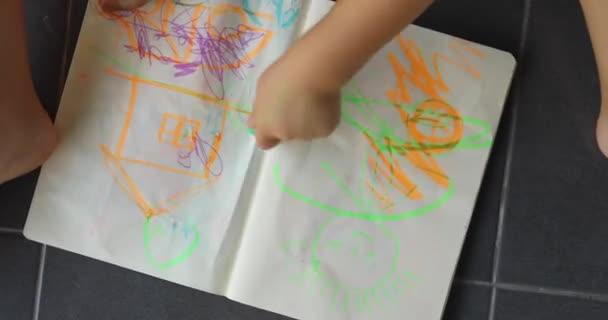 Dětské ruce kreslí barevné značky na papíře vleže na podlaze pohled shora