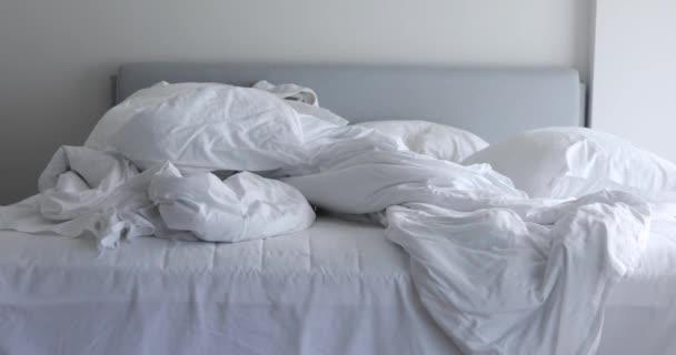 Neustlané postele s bílým ložním prádlem