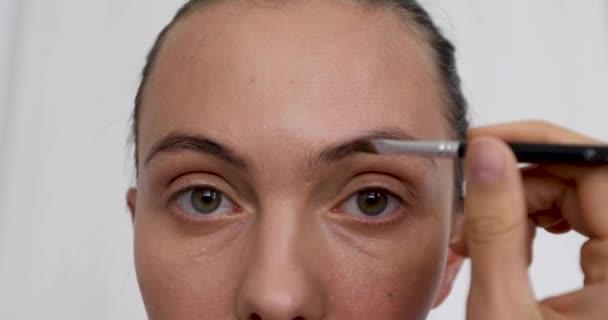 Closeup of woman doing makeup of eyebrows