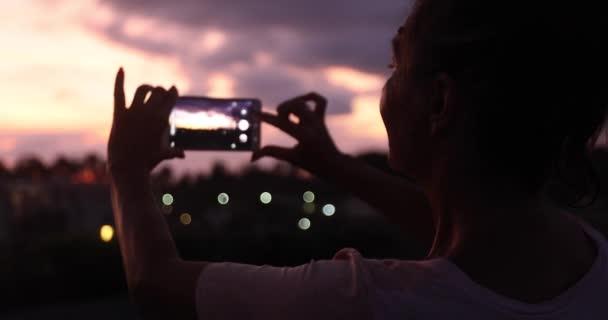 Woman taking photo of sunset sky