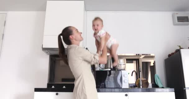 Happy mother throws baby white kitchen background
