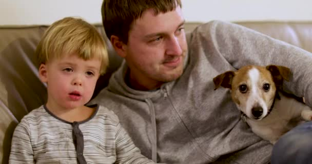 Father with son dog are sitting sofa