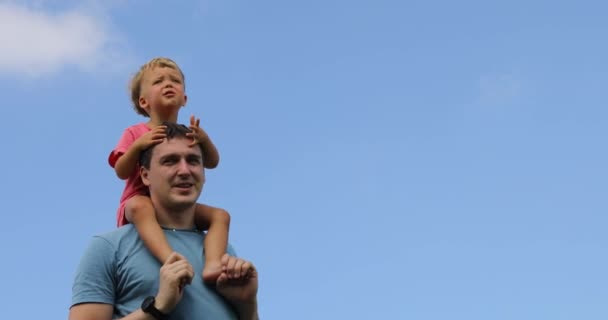 Child sits on shoulders of his father against blue sky