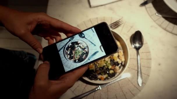 Person fotografiert Essen am Telefon beim Abendessen