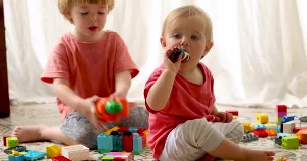 Bratr a sestra hrají plastové bloky