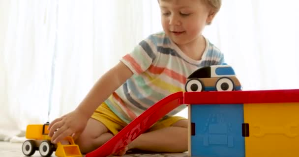 Three years old child boy play with wooden toy cars