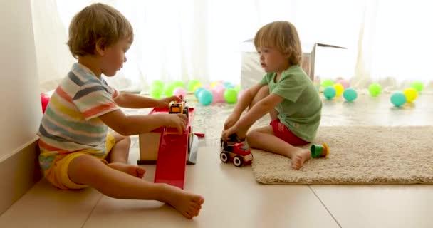 Batolci sedící na podlaze a hraní hraček