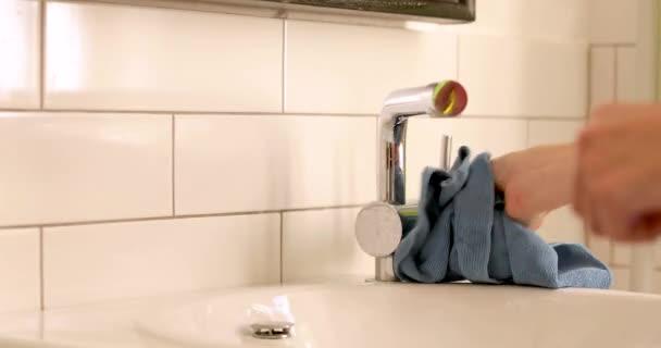 Személy törölgetve csaptelep törülközővel a fürdőszobában