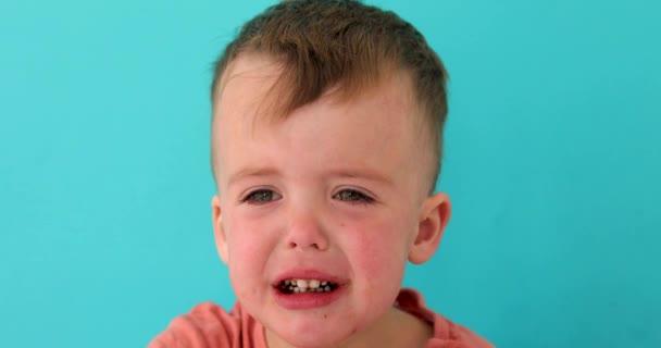 Inconsolabile piangere sconvolto bambino guardando la fotocamera