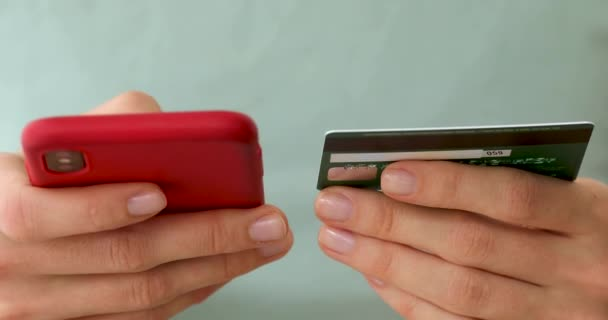 Womans hands holding a credit card and using cell phone