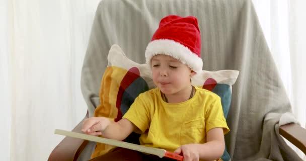 Kleiner Junge mit roter Weihnachtsmütze liest orangefarbenen Bucheinband