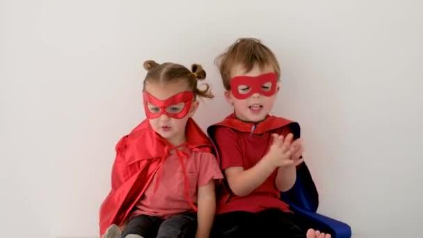 Vicces fiú és lány szuperhősökben jelmezek tapsolnak.