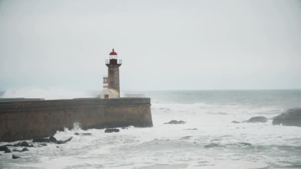 Silné vlny přestávka o molo, maják na pobřeží Atlantského oceánu