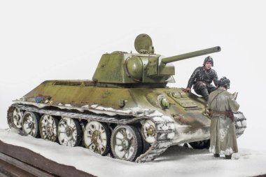 Soviet tank T 34 76 production UVZ, during the Second world war, the crew gets the job. The time period in the winter of 1942. Diorama in modeling, made by the author of the photo.