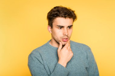 Puzzled bewildered man thinking over smth or contemplating. scratching his beard. portrait of a young brunet guy on yellow background. emotion facial expression. feelings and people reaction concept. stock vector
