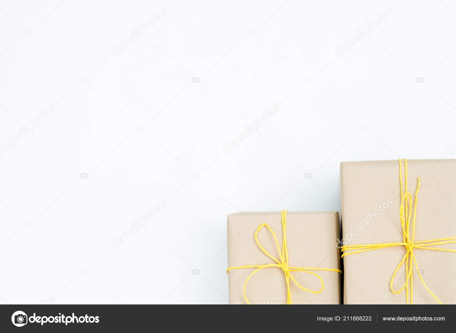 23704b94a0e6 Cadeaux de Noël dans des boîtes-cadeaux emballés dans du papier craft et  attaché avec une ficelle jaune. deux paquets sur fond blanc avec espace  libre ...