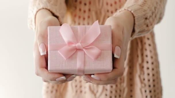 Dívka drží současné růžová Dárková krabice ženské odměnu