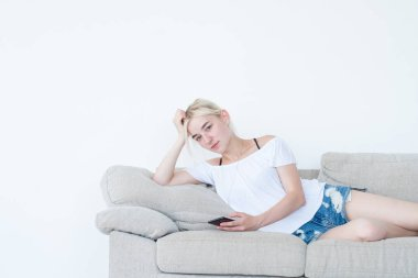 woman laying couch phone idle lifestyle addiction