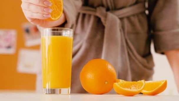 woman bathrobe squeezing orange glass breakfast