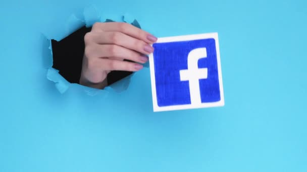 Facebook logo global communication hand paper hole Royalty Free Stock Video