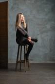 Aranyos lány felső, bőr rövidnadrágot és sűrű harisnya ül a széken, lábát közelében paraván