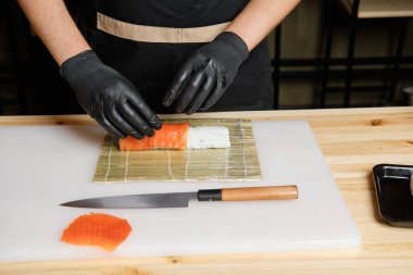 Male hand put salmon while preparing rolls