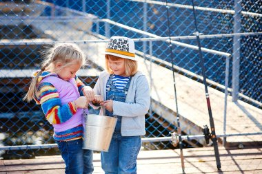 Two happy laughing children with fishing rods and a bucket on a fishing trip on a wooden pontoon on a fish farm
