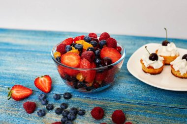 Muffin lie on a large white plate standing next to a deep glass bowl with a salad of fresh berries